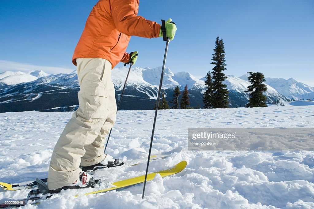 Male skier crossing field in winter, side view, low section