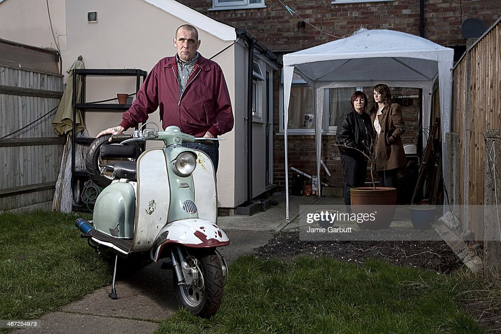 Male skinhead with scooter and family : Stock Photo
