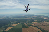 Male skydiver freeflying upside down above Siofok, Somogy, Hungary