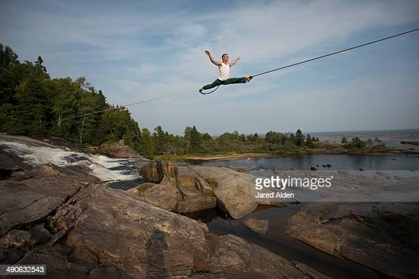 Male slackliner doing the splits on a long highline over water
