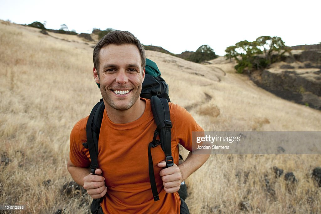 Male smiles while hiking in the outdoors. : Stock Photo