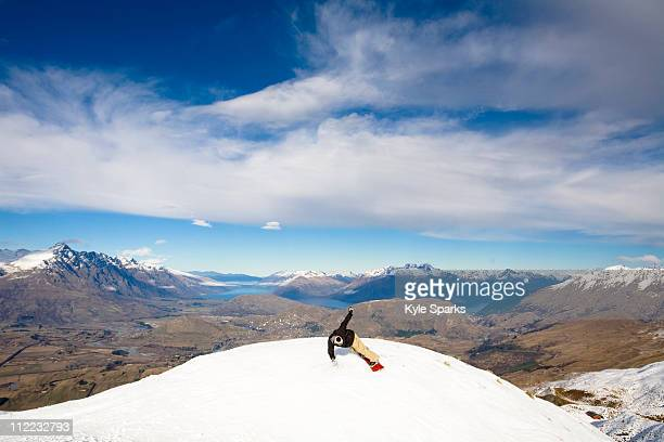 A male snowboarder blasts a heel side turn while snowboarding in Queenstown, New Zealand.