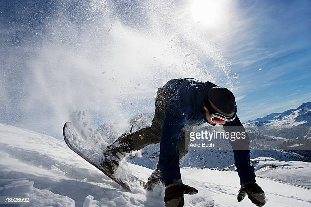 male snowboarder falling over on mountain