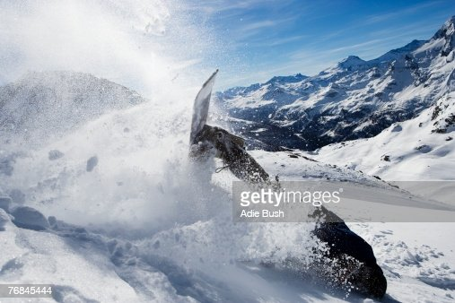 Male snowboarder falling over on mountain : Stock Photo