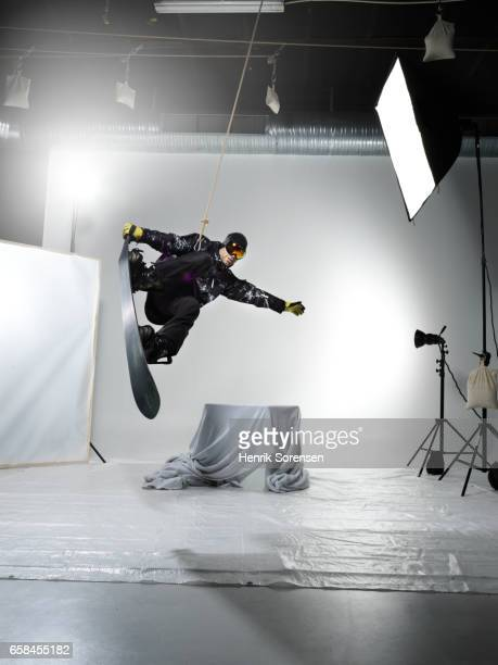 Male snowboarder in the air in a studio