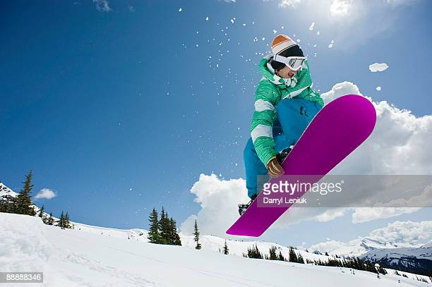 male snowboarder jumping in air