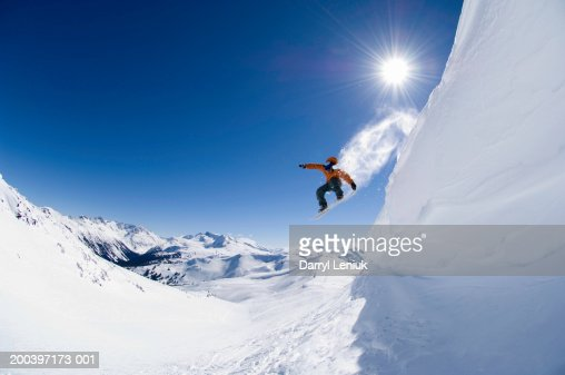 Male snowboarder jumping off cornice, low angle view