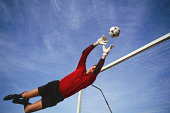 Male soccer goalie leaping to make a save in front of goal
