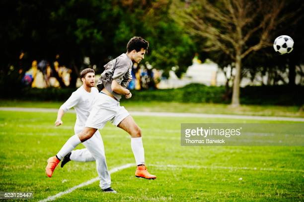 Male soccer player heading ball past opponent