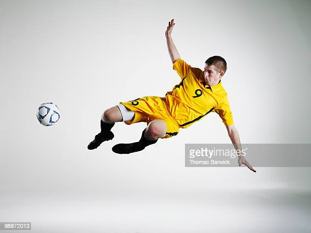 Male soccer player jumping in mid air to kick ball