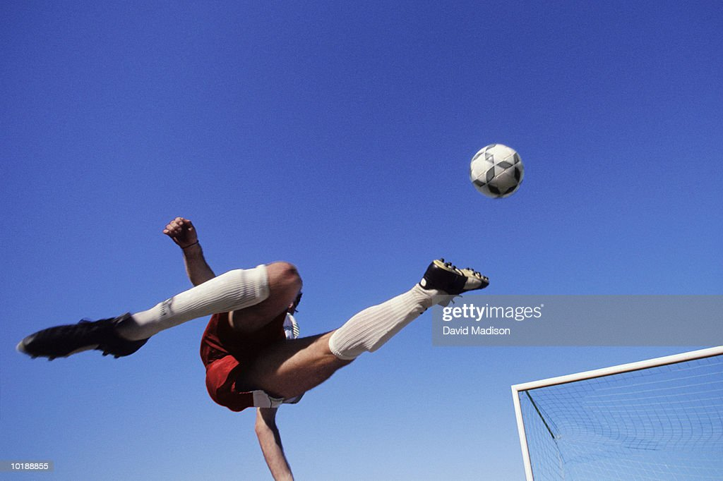 Male Soccer Player performing bicycle kick near goal, view from below : Stock Photo