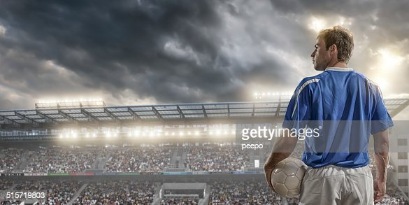 male soccer player standing in front of a large crowd