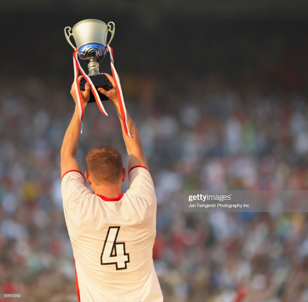 Male soccer player triumphantly holding up trophy : Stock Photo