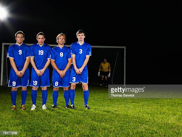 Male soccer players in defensive wall awaiting free kick