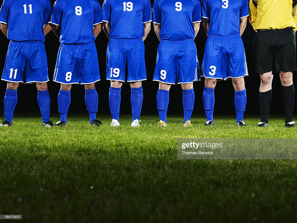 Male soccer team standing in line, hands behind back : Stock Photo