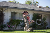 Male soldier hugging and lifting wife in garden on homecoming