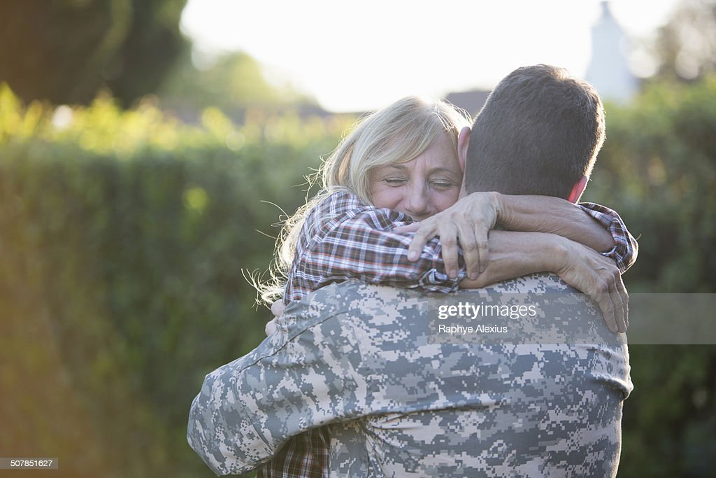 Male soldier hugging mother on street at homecoming