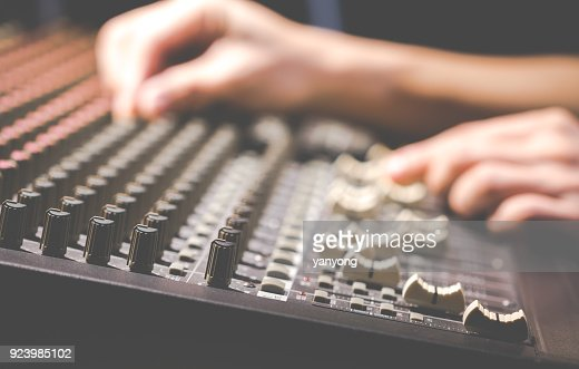 male sound engineer hands working on audio mixing console : Stock Photo
