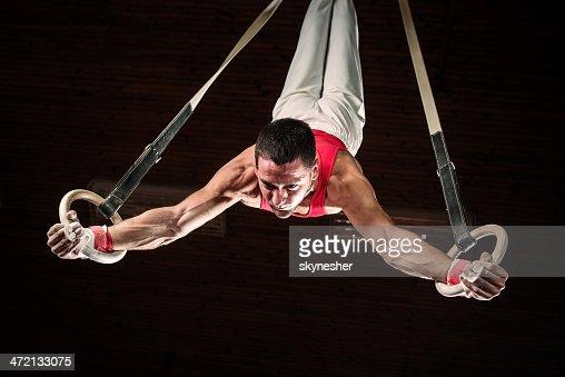Male sportsman on gymnastics rings.