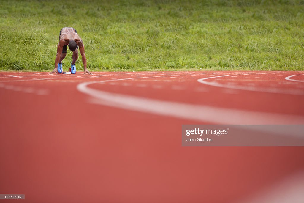Male sprinter in blocks, awaiting starting gun : Stock Photo