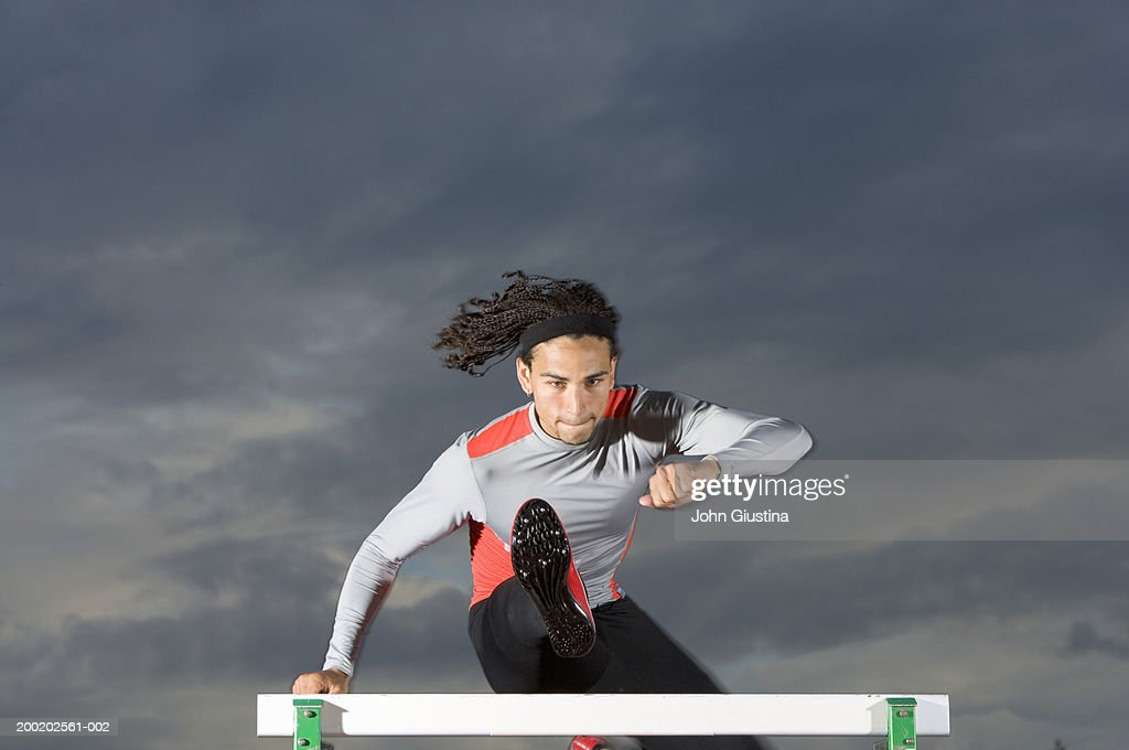 Male sprinter leaping over hurdle : Stock Photo