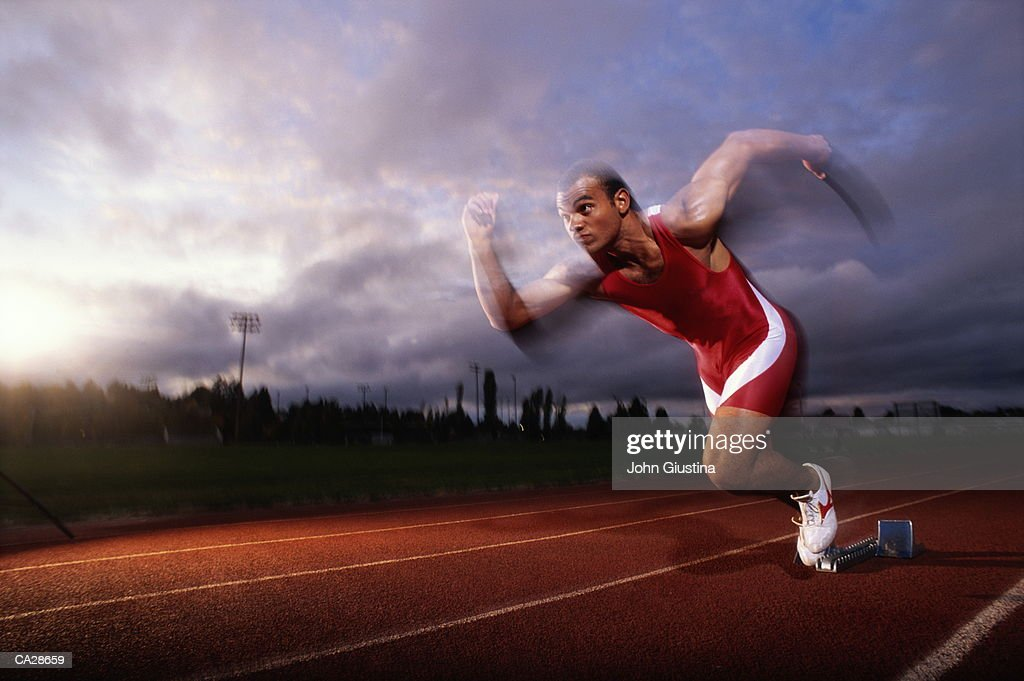 Male sprinter leaving starting block (blurred motion) : Stock Photo