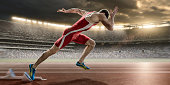 A close up image of a professional powerful male sprinter in mid action sprinting out of starting blocks at high speed, on a running track. The action takes place in a generic outdoor floodlit athleti