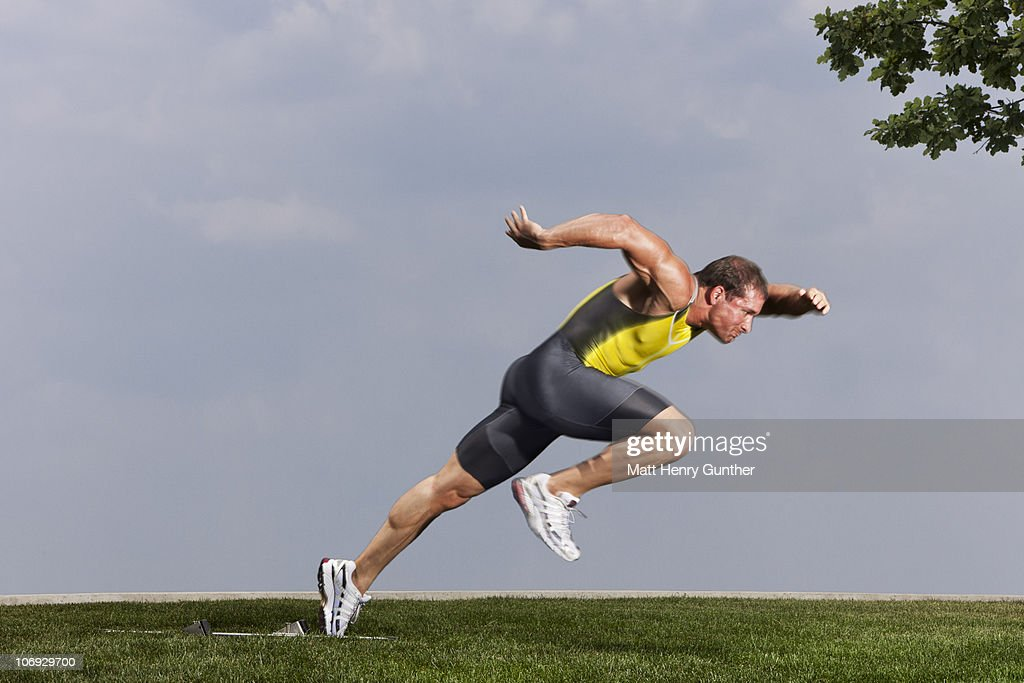 Male sprinter taking off from starting blocks : Stock Photo