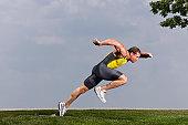 Male sprinter taking off from starting blocks