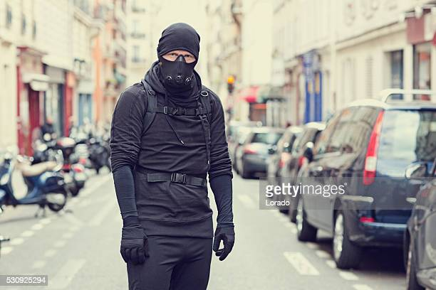 Male standing in black in Paris street wearing breathing apparatus