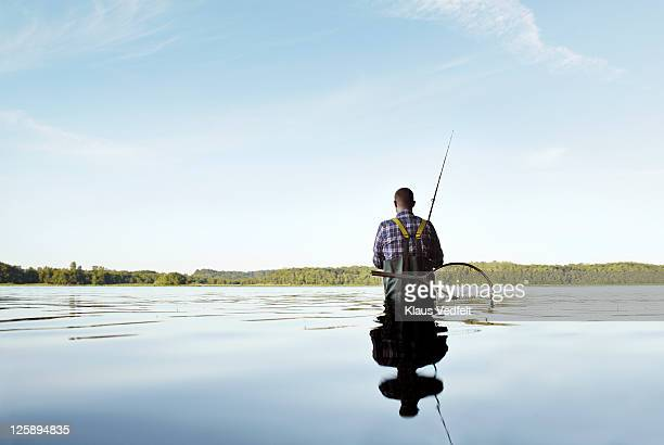 Male standing in water fishing surrounded by trees