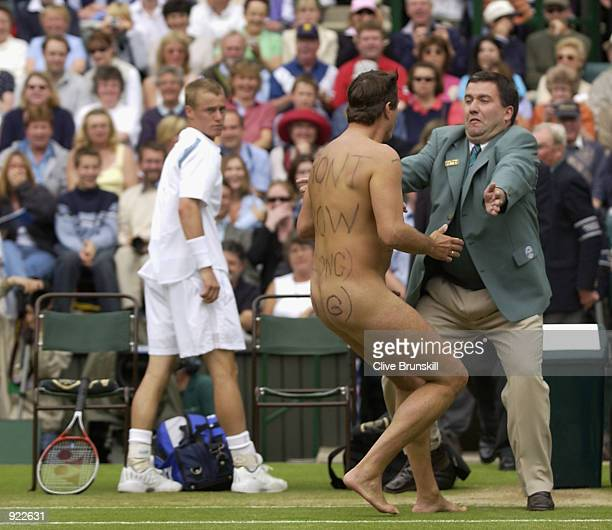 A male streaker runs onto Centre Court as Lleyton Hewitt of Australia plays David Nalbandian of Argentina during the Mens Singles Final at the All...