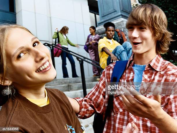 Male Student Chatting Up an Embarrassed Looking Girl at the Bottom of Steps Outside a School Building