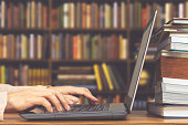 male student hands making research on laptop and browse internet for preparing exam and learning lessons in library