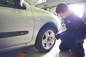 Male student mechanic tightening car wheel in college garage