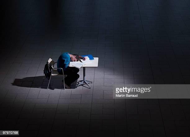 Étudiant mâle dormir au bureau pour travailler dans l'obscurité
