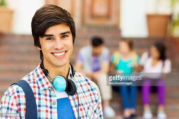Male Student With Students Sitting In Background On College Camp