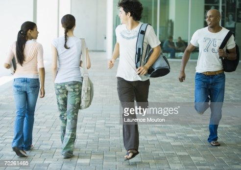 Male students running across campus, looking back at female students
