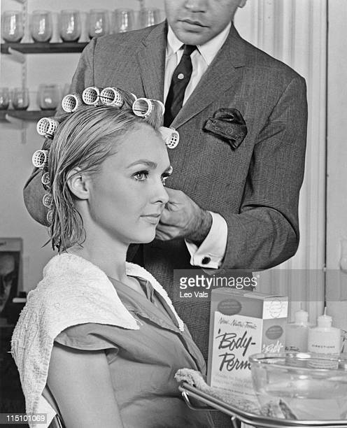 A male stylist preparing a young woman's hair for a body wave perm by first rolling her hair with curlers and then applying formula in the 1960's