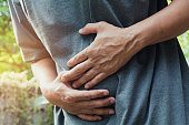 Male suffering from stomachache pain,A man stomachache at outdoor,Healthy concept.