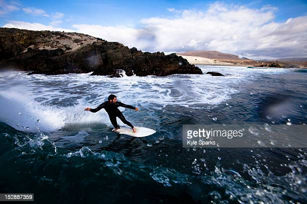 A male surfer bottom turns around a breaking wave while surfing in Northern Baja, Mexico.