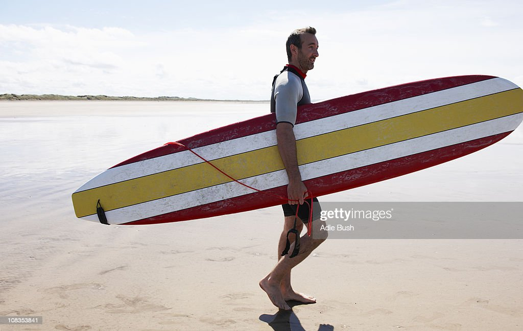 Male Surfer carrying board on beach : Stock Photo