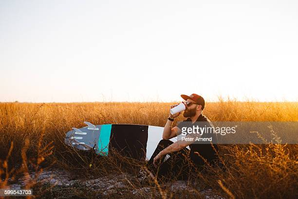 Male surfer drinking coffee in field of long grass at sunset, San Luis Obispo, California, USA