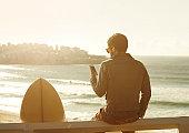 Male surfer in Bondi, using phone
