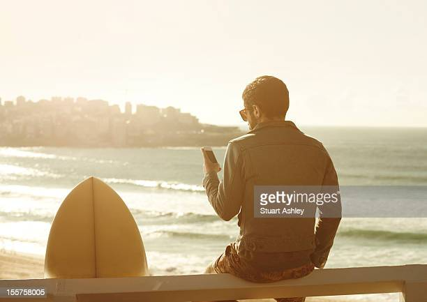 Male surfer in Bondi, using phone