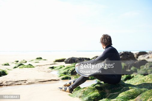 Male surfer looking out toward sea. : Stock Photo