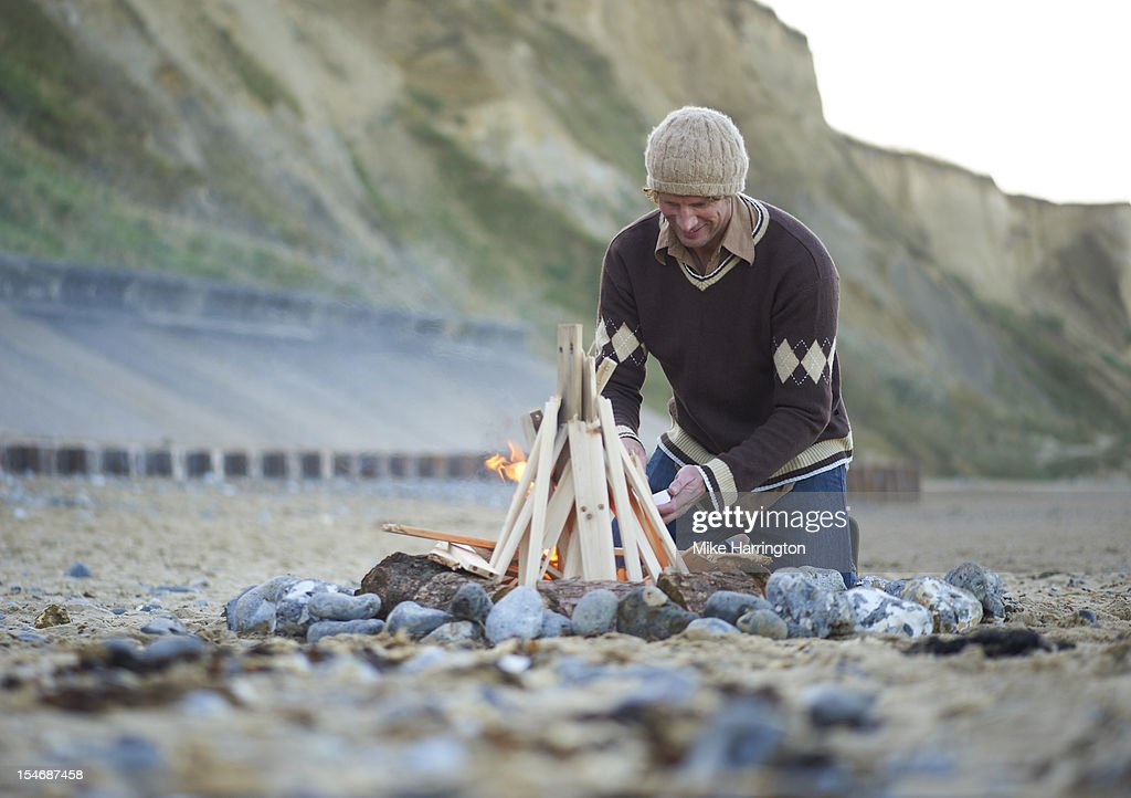 Male surfer making fire on beach : Stock Photo