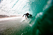 A male surfer pulls into a barrel while surfing at Zuma beach in Malibu, California.
