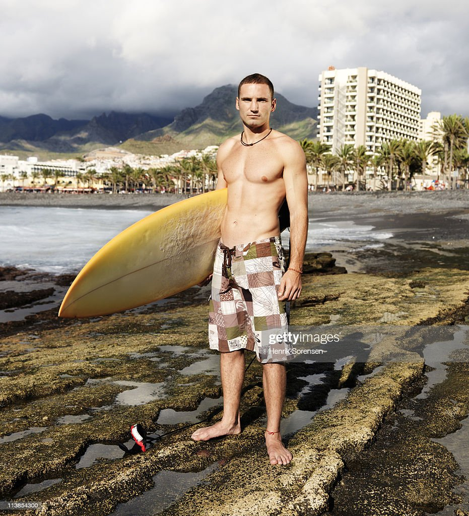 Male surfer standing waiting holding a surf board : Stock Photo