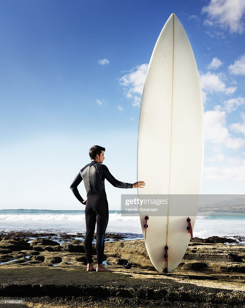 Male surfer standing with an oversized surf board : Stock Photo